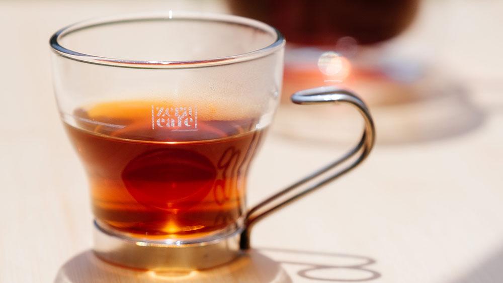 一杯精品咖啡裝在玻璃杯中,暖陽映襯
