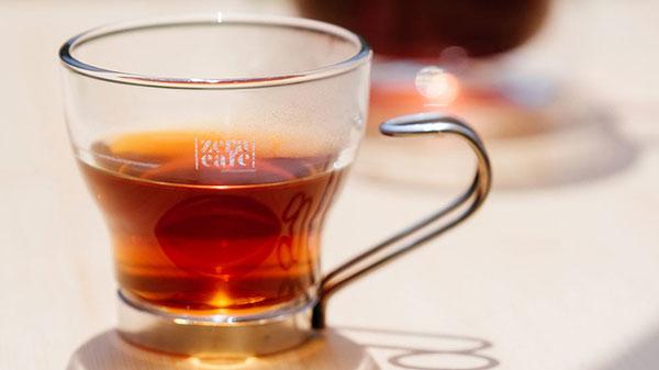 精品咖啡裝在小玻璃杯中,陽光斜灑照出琥珀色光芒