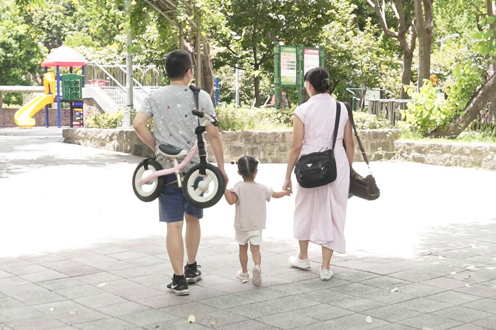 一家人開心地牽著手,背著rollybike一起出遊
