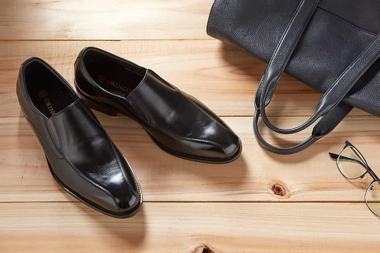 黑色商務樂福皮鞋與公事包擺放在木板上