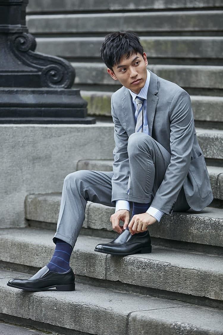 穿著淡灰色西裝搭配樂福皮鞋的模特坐在石階上