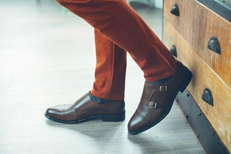 模特穿著深咖啡雙扣孟克皮鞋搭配橘色休閒褲