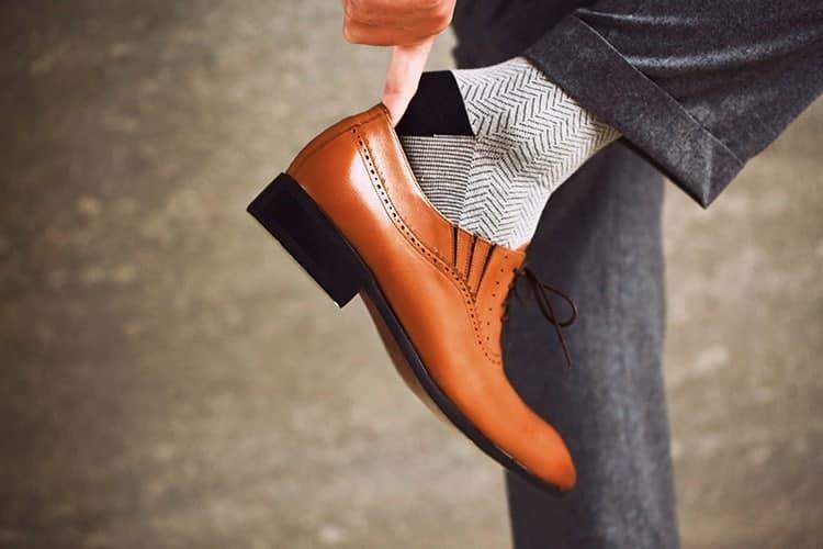 模特抬起右腳並使用右手指當鞋拔幫助穿上咖啡色牛津鞋