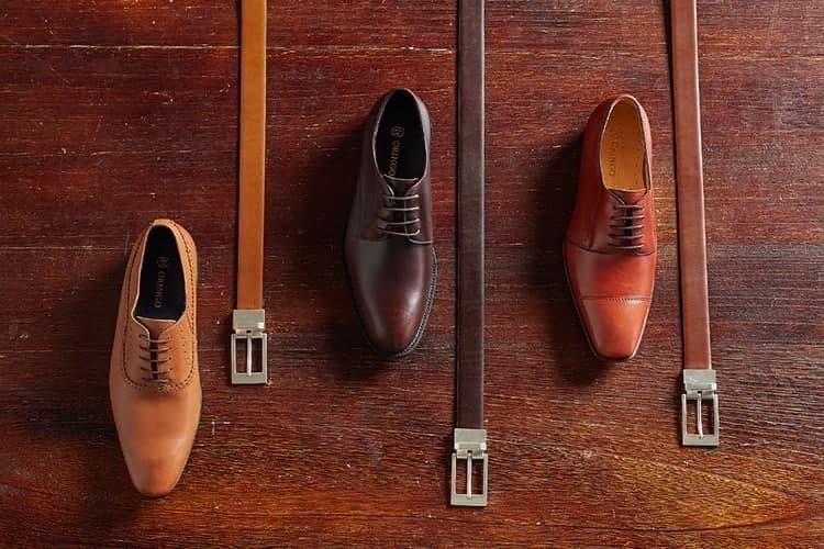 俯視三色皮帶 -紅棕 密棕 深棕-與三雙牛津鞋依序展示在木頭桌面上