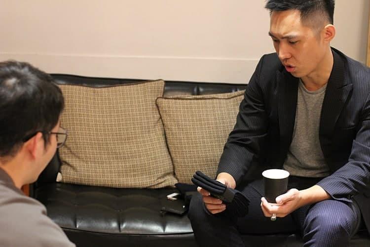 坐在在黑色皮沙發上的客人仔細查看右手上的紳士襪商品