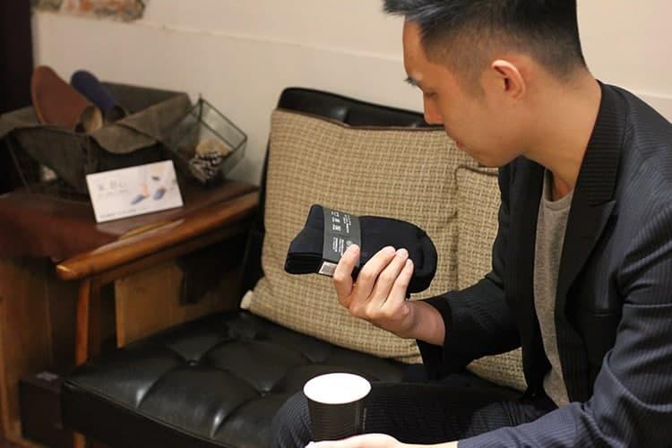 坐在在黑色皮沙發上的客人仔細查看手中紳士襪包裝上的詳細介紹