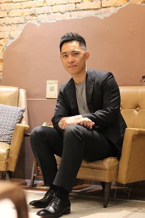 坐在淺色皮沙發上的林果老客人Sam身穿黑西裝配上黑色德比鞋
