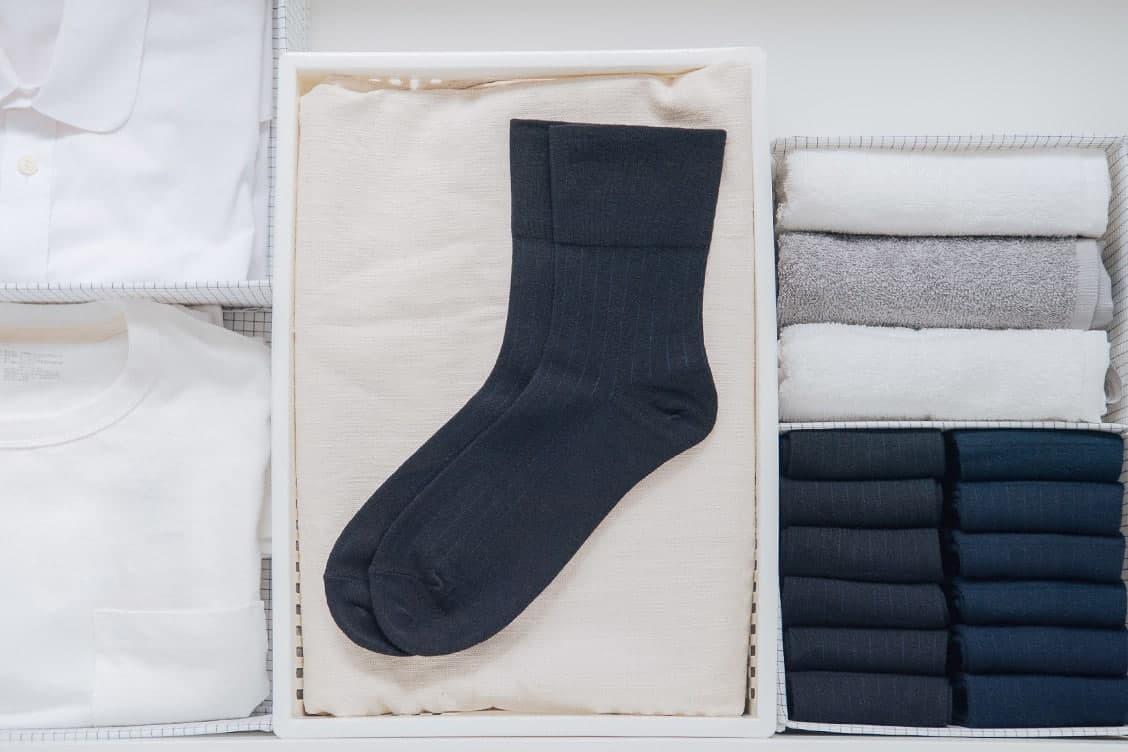 素色的黑色紳士襪平放在衣櫃的白色置物籃中