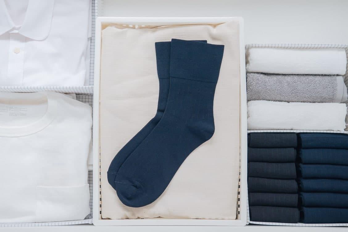 素色的海軍藍色紳士襪平放在衣櫃的白色置物籃中