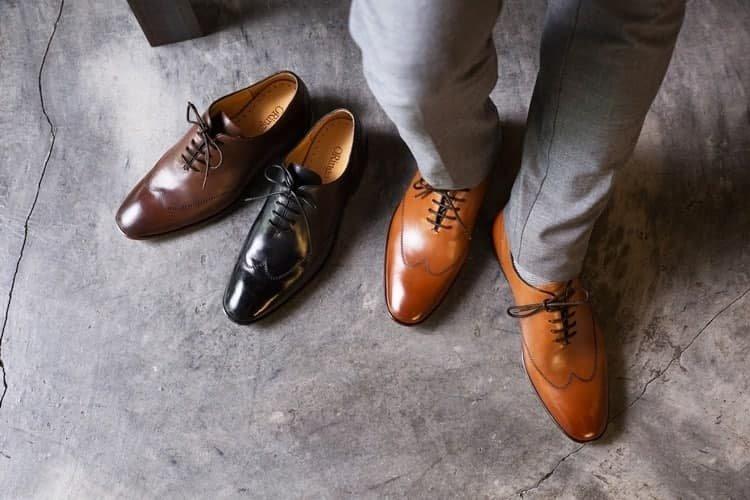 3色Wholecut翼紋縫線牛津鞋黑色、咖啡色、蜜棕色展示在灰色水泥地上