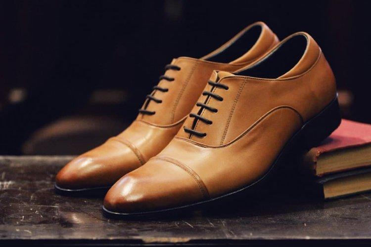 膠底的基本款蜜棕色牛津鞋墊著書本擺在深咖啡的桌面上