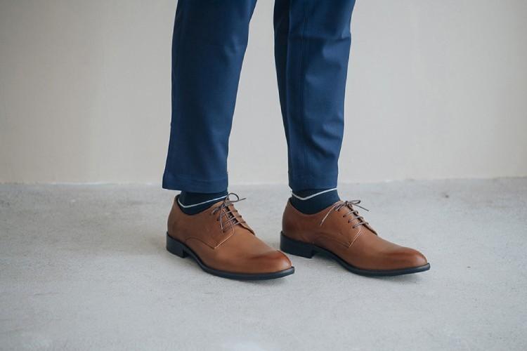 特寫穿著湛藍色西裝褲的模特搭配上德比鞋咖啡色站在米色的牆面前