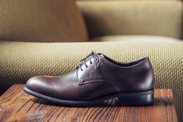 單只基本款膠底德比鞋濃淬咖色置放在米色沙發前