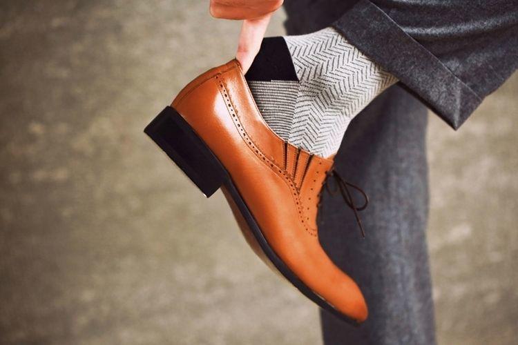 特寫模特單腳穿上側邊有隱藏式鬆緊帶設計的咖啡色商務牛津鞋