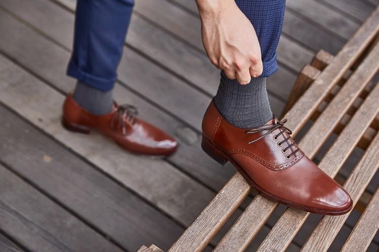 藍色褲子與咖啡色牛津鞋與黑色襪子