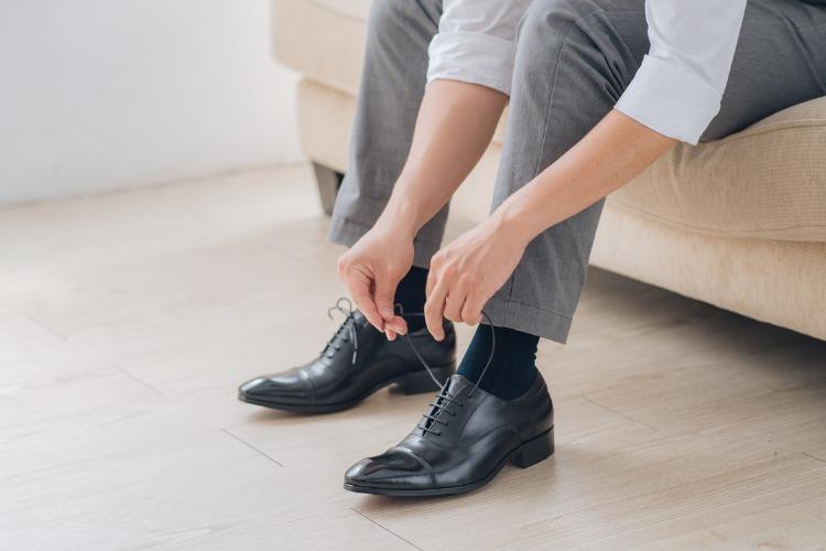 穿灰色西裝與黑色牛津鞋正在綁鞋帶的男人