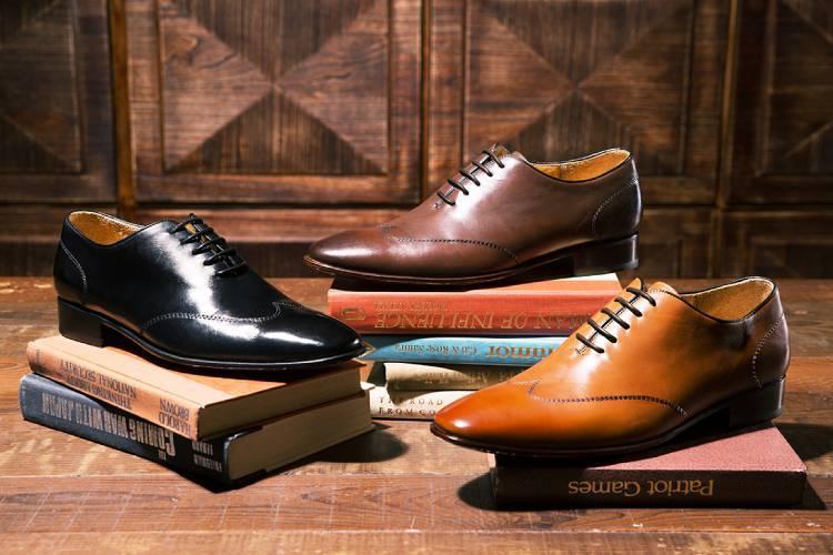 單只黑色蜜棕色咖啡色翼紋縫線牛津鞋交錯墊著書疊放在木紋地板上