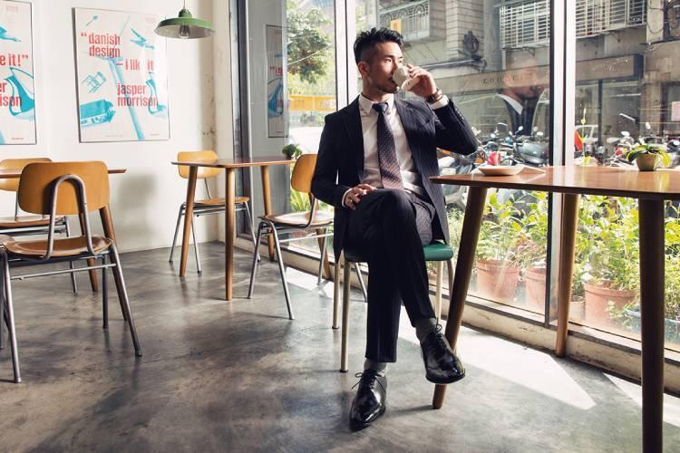 穿著黑色西裝的模特搭配黑色皮底翼紋牛津鞋坐在落地窗邊品嘗左手手上的咖啡