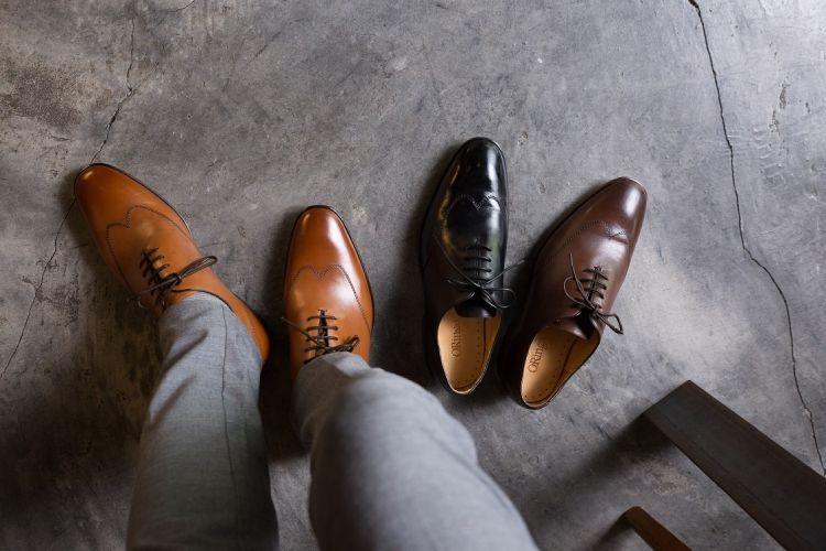 特寫俯視穿著灰色西裝褲的模特搭配蜜棕色皮底翼紋牛津鞋與展示單水泥地上的單只黑色和咖啡色牛津鞋