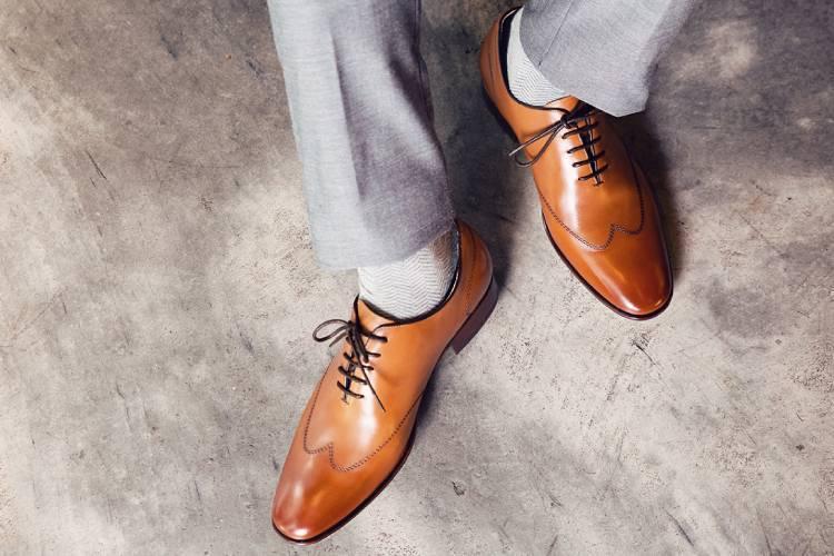 特寫穿著淺灰色西裝褲的模特搭配蜜棕色皮底翼紋牛津鞋