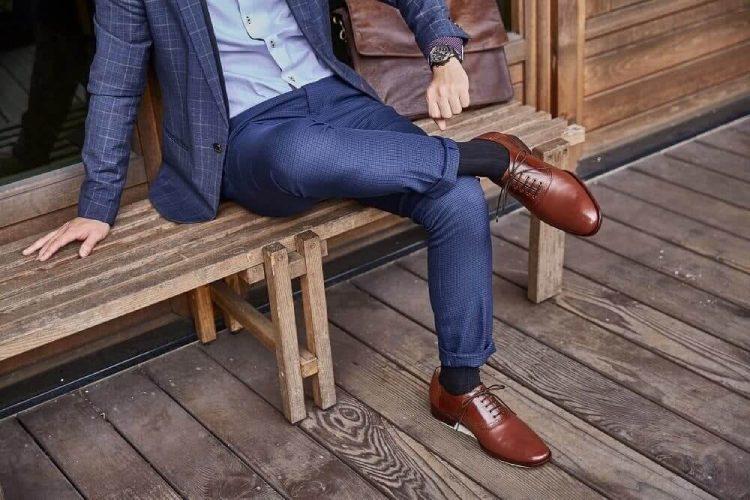 穿藍色西裝與咖啡色鞍部牛津鞋的模特坐在長木椅上看著左手的手錶確認時間
