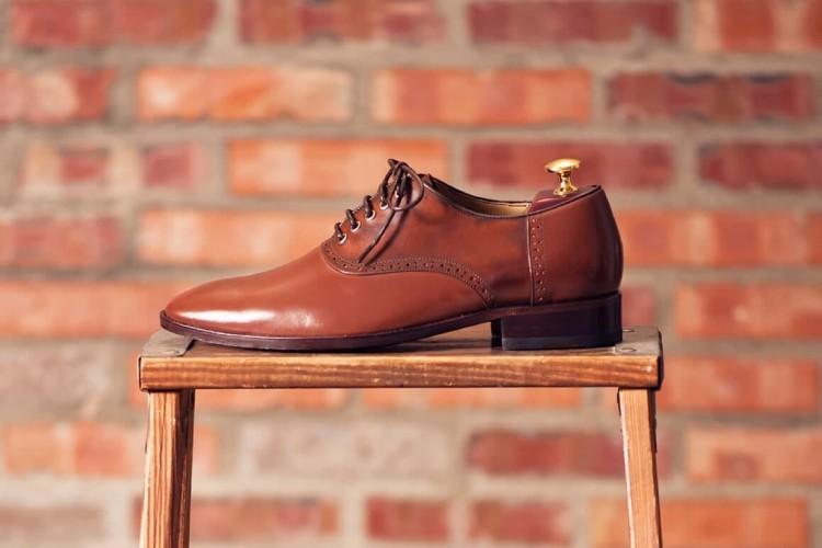 左腳單只咖啡色鞍部牛津鞋外側展示於木椅上