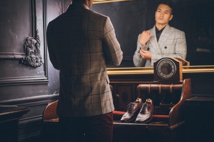 一雙鞍部牛津鞋擺放在專著灰色個紋外套面對鏡子調整袖扣的模特前方的木桌上