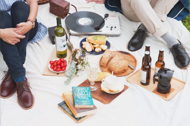 穿著布呂歇爾皮底鞋坐在白色餐墊上享受白酒麵包與書本愜意的草地上的野餐時光