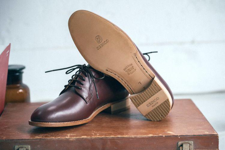 一雙布呂歇爾皮底鞋勃艮第酒紅色左腳鞋底朝前展示在木箱上