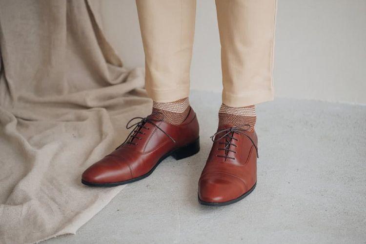 腳部局部特寫穿著卡其色休閒褲搭配栗棕色牛津鞋基本款的模特兒