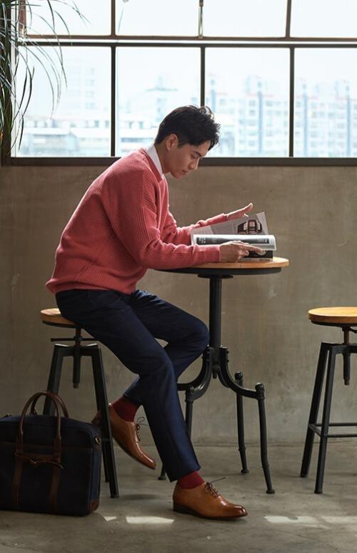 穿粉紅上衣與藍色西裝正在看書的男人