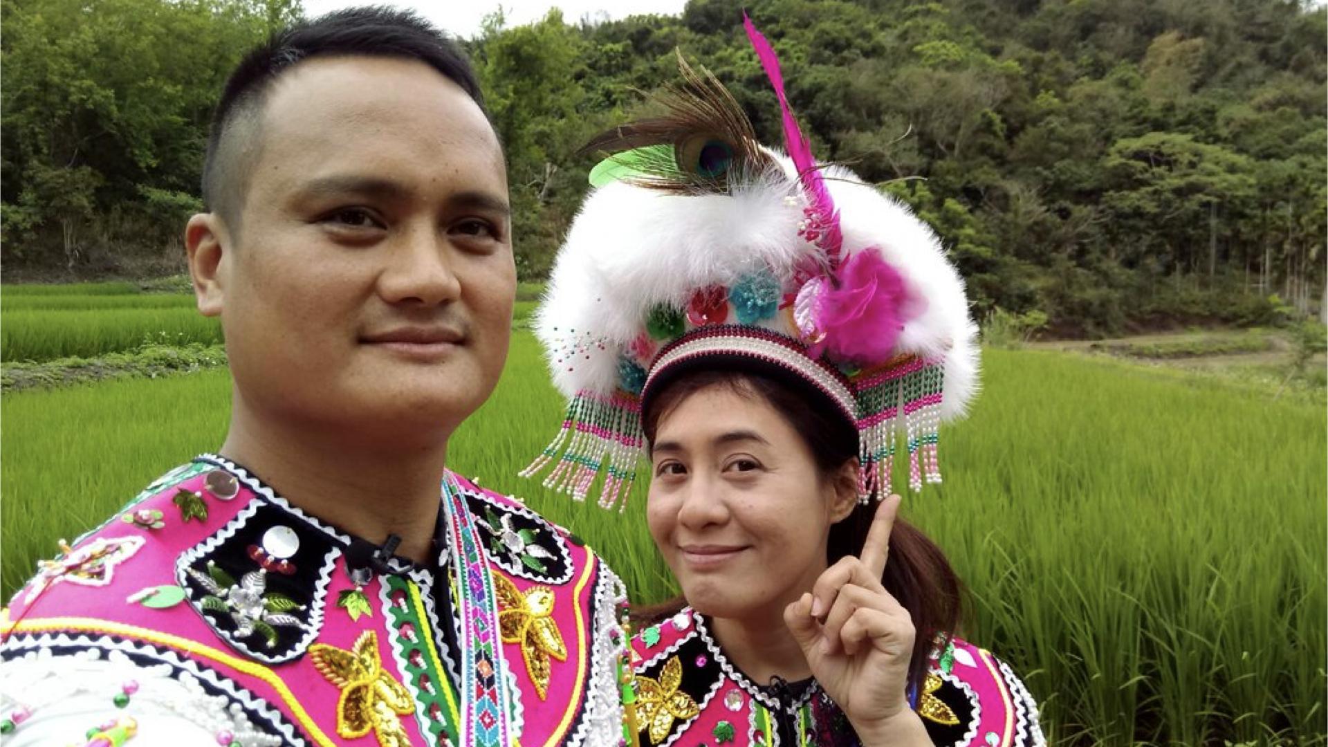 一對原住民原住民夫妻,身穿原住民傳統服飾與帽子,開心的與大自然合照