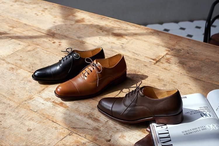 木桌面上展示著3只鵝頸橫飾皮底商務牛津鞋黑色、棕色與咖啡色
