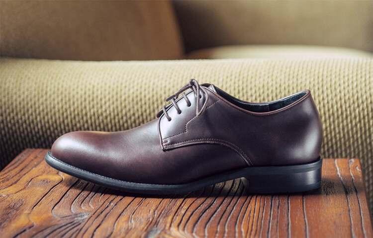 深咖啡色德比鞋放木桌上