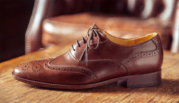 深咖啡雕花牛津鞋放在木桌上
