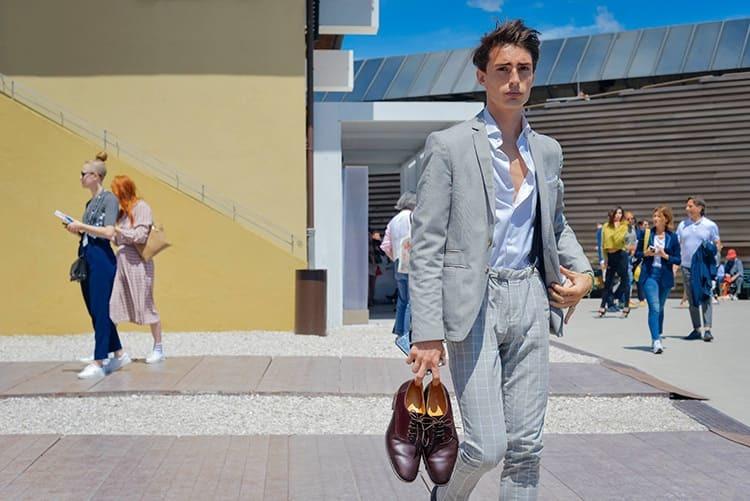 穿著灰色西裝外套與灰色格紋長褲與手拿牛津鞋的男人