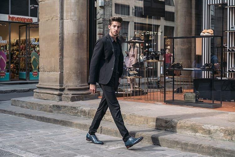 穿著黑色全套西裝與藍色牛津鞋的男人