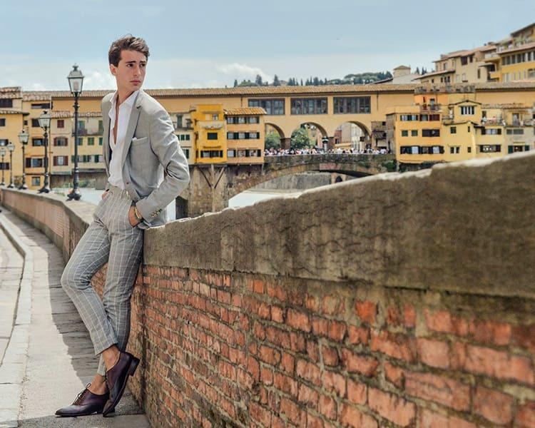 穿著灰色西裝外套與灰色格紋長褲與牛津鞋的男人
