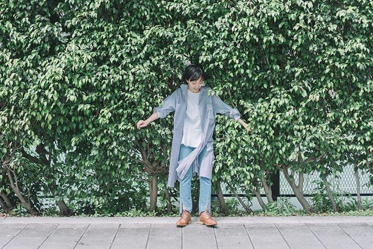 穿著灰色大衣與單寧長褲與靴子的少女