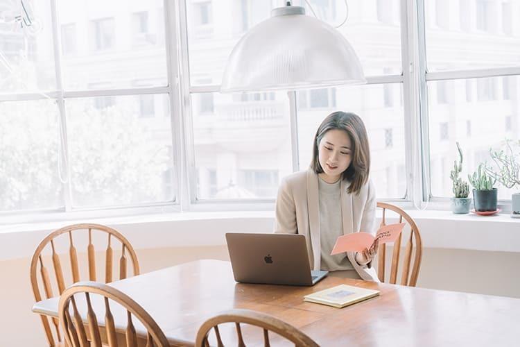 穿著卡其針織上衣正在用電腦的少女