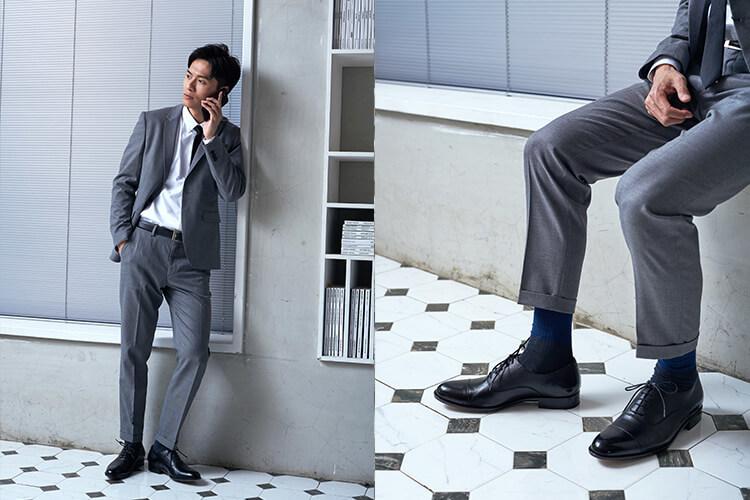 穿著灰西裝與牛津鞋的男人靠牆講電話