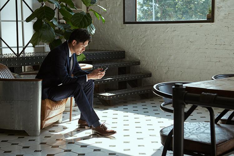 一名男人穿深藍西裝和牛津鞋滑手機