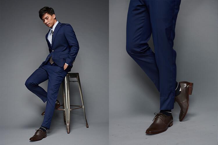 一名穿深藍西裝和德比鞋的男人