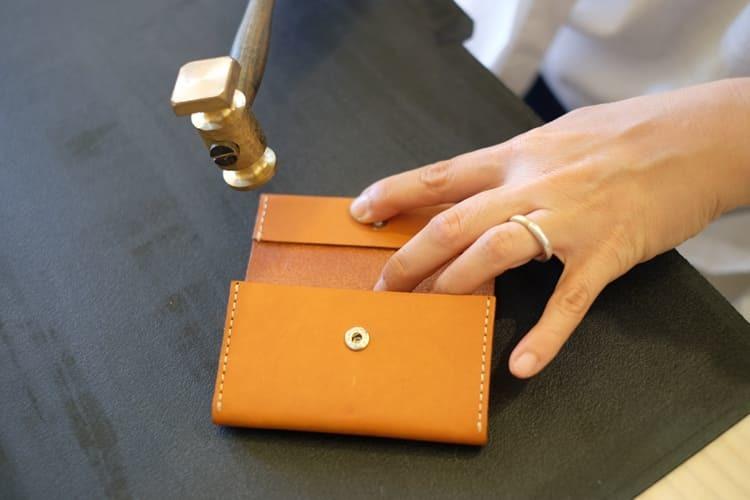 利用銅槌示範將邊角縫合處的皮料更緊密