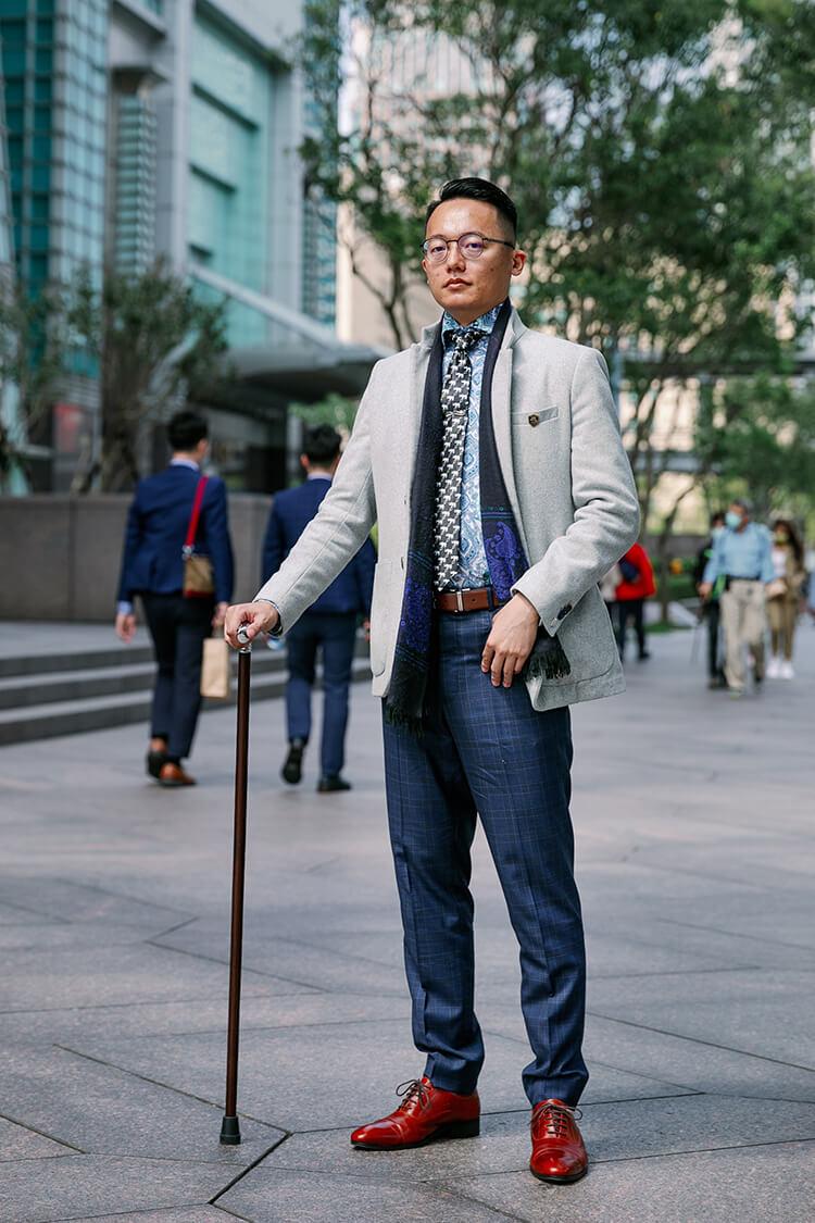 拄著拐杖與藍色褲子跟紅色皮鞋的男人