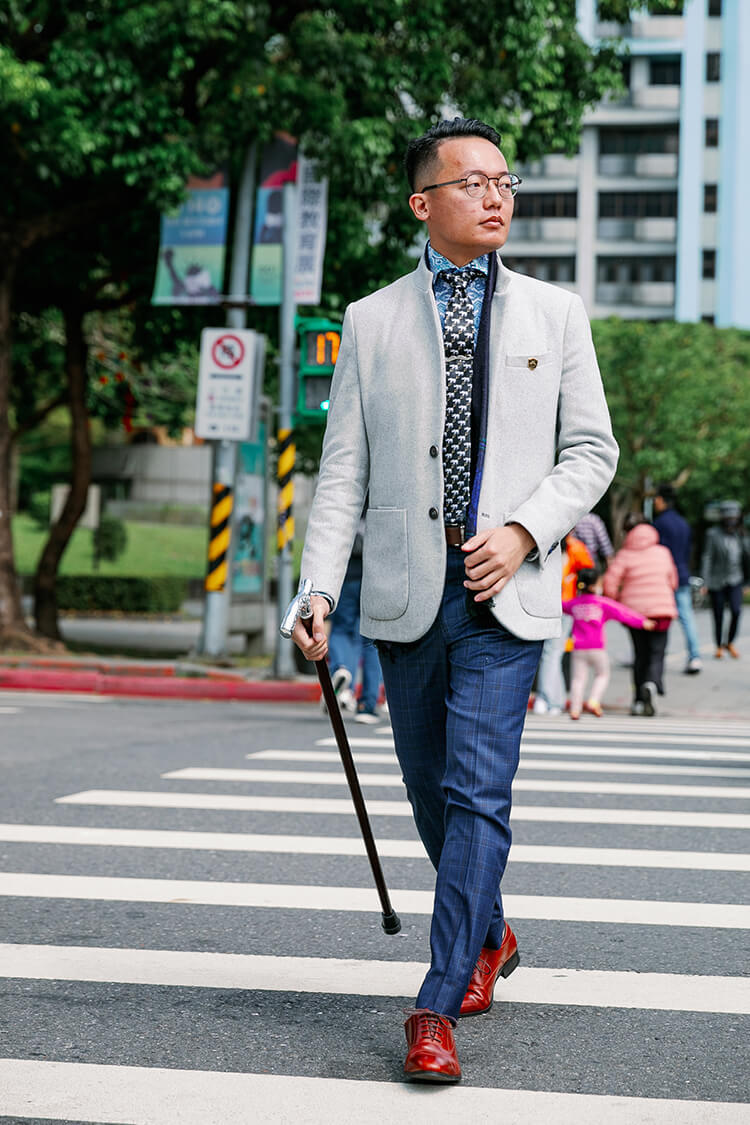 穿灰色西裝外套與藍色褲子與拐杖正在過馬路的男人