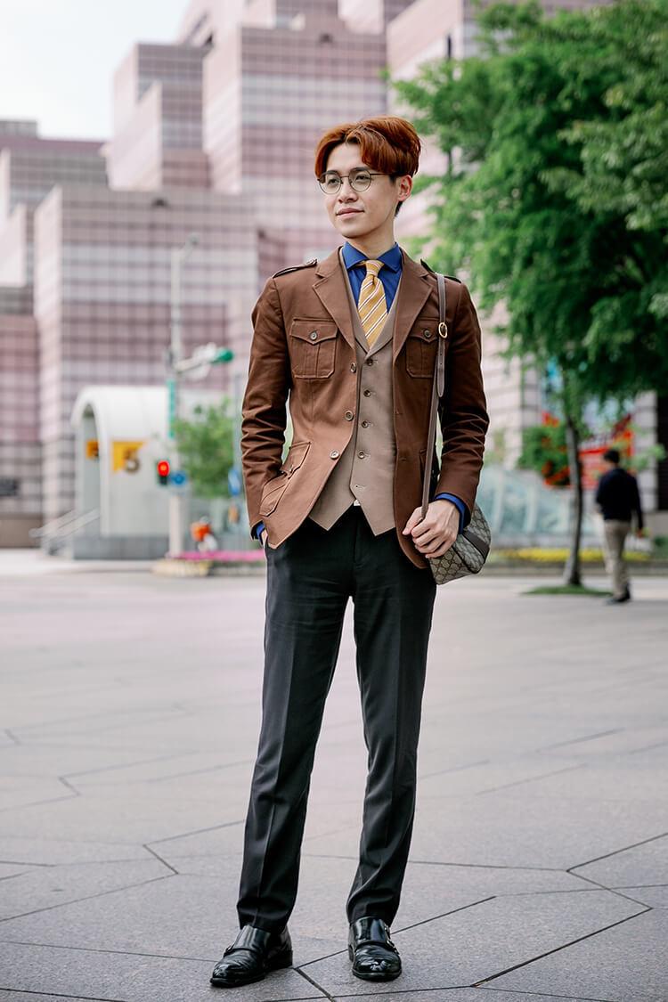 穿著咖啡色西裝外套與黑色褲子跟黑色孟克鞋的男人