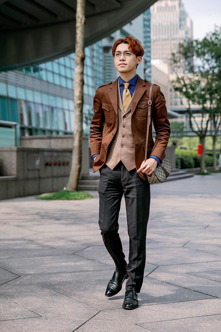 穿著咖啡色西裝外套與黑色褲子跟黑色孟克鞋正在走路的男人