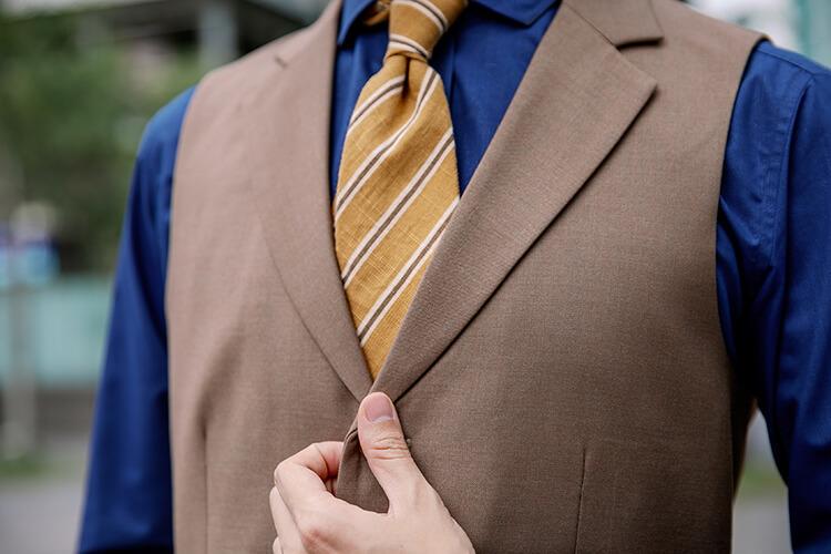 穿著藍色襯衫與咖啡色背心與黃色領帶的人