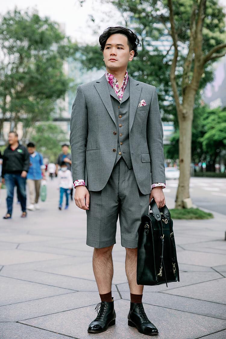 穿著灰色西裝與黑色靴子的男人